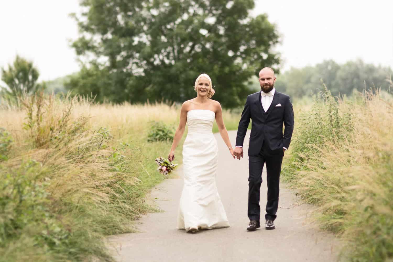 Brautpaar auf einem Weg zwischen Wiesen vom Hochzeitsfotograf Hannover